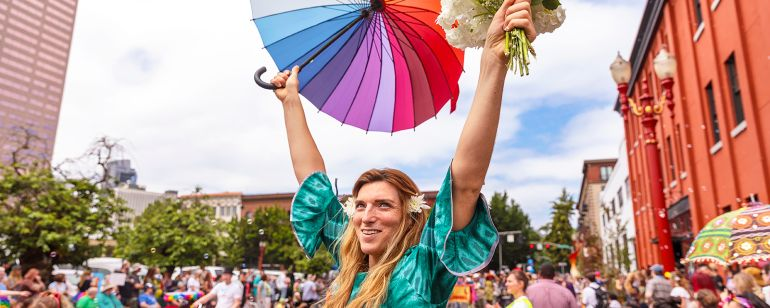 person holding up bouquet of flowers and rainbow flag during parade in a street parade