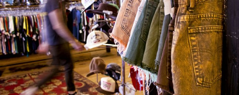 racks of clothing and hats on display at the Red Light Clothing Exchange