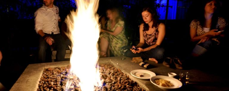 people sitting around a fire pit at night
