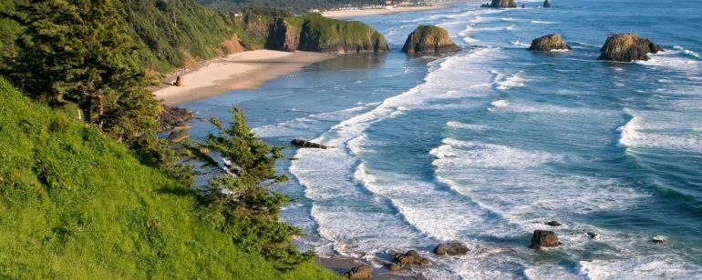 view overlooking Ecola Point, ocean waves crashing on the beach wit h large rock formations