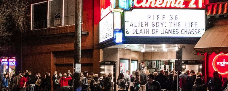 A crowd of move goers gather beneath the Cinema 21 marquee at night