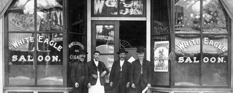 a black and white photo of three men standing in front of a saloon