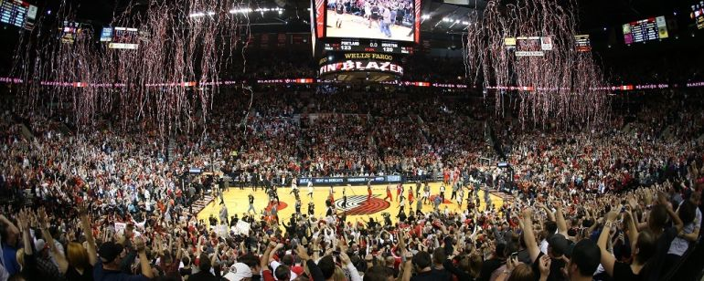 Streamers rain down over a basketball court and thousands of fans