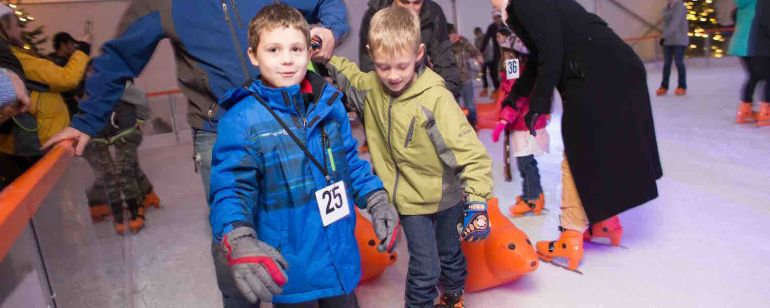 two children and a man on ice skates