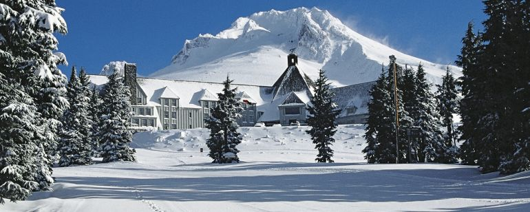 Timberline lodge covered in snow on a sunny day