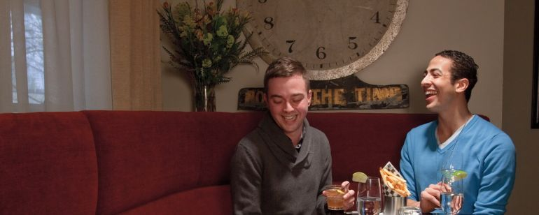 a couple laughing over dinner and drinks in a red corner booth
