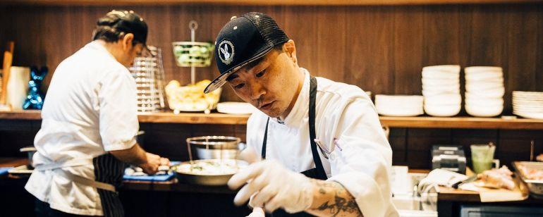 a cook prepares food in a pan