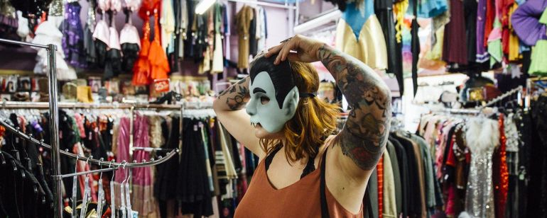 a woman trying on a vampire mask at a costume store