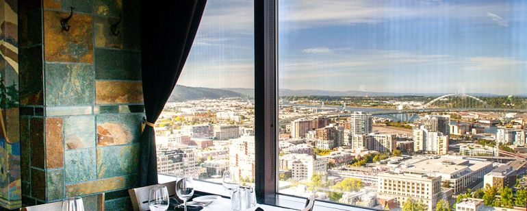 A table set with a white tablecloth next to a window with a scenic city view