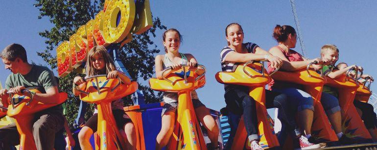 Smiling children riding the colorful, retro Disk'O at Oaks Amusement Park.