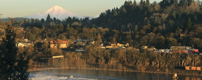 Sunset's orange glow bath Mt. Hood's snow capped peaks, Oregon City's homes and Willamette Falls' frothy waters.