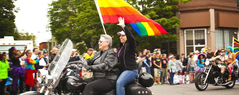 Two pride parade participants on a motorcycle with a rainbow pride flag