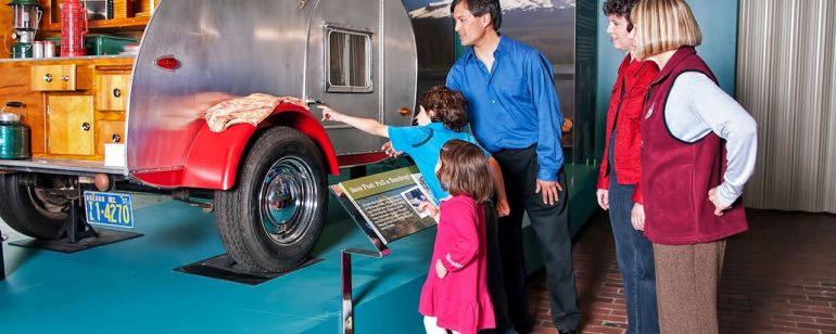 a family looking at a camping vehicle on display at the Oregon History Museum