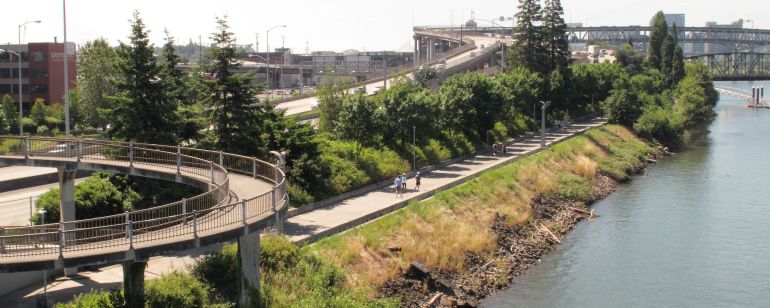 Three people use a riverside path flanked by a highway