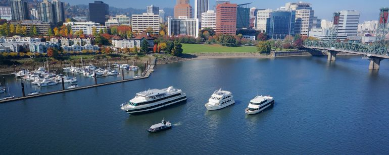 four cruise ships of varying sizes on the Willamette River