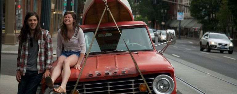 two people next to an orange truck with a canoe strapped to the top