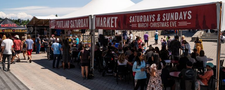 """People stand under a canopy with signs reading \""""Portland Saturday Market Saturdays & Sundays March - Christmas Eve\"""""""