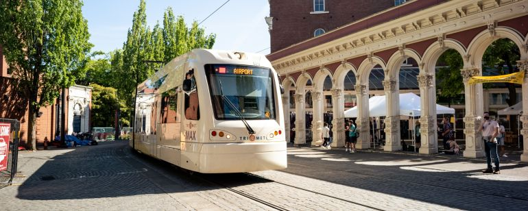 Light rail train car driving past people shopping at an outdoor market