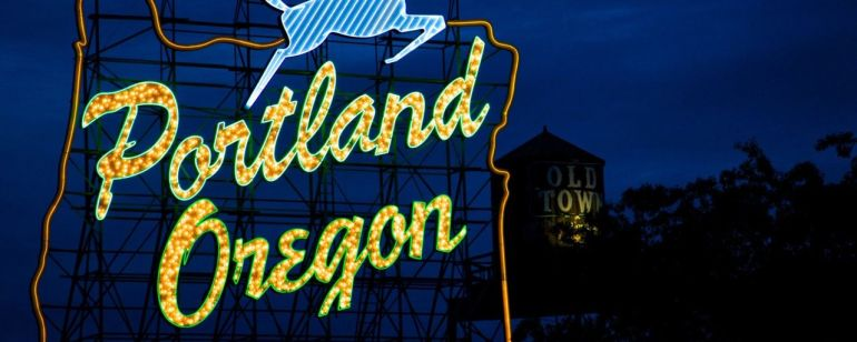 A sign made of light bulbs form the silhouette of the state with a stag jumping over the words Portland Oregon