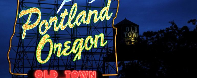 """a neon light sign reading \""""portland oregon old town\"""" with a deer leaping over the words"""
