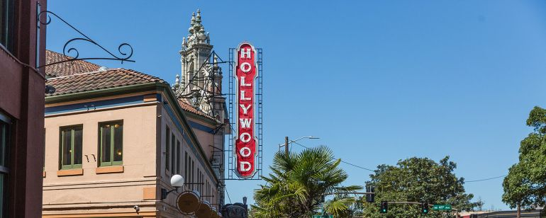 people walking on the sidewalk under a vintage Hollywood Theater sign