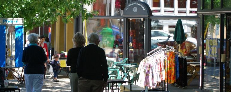 tables and shop items displayed on the sidewalk as people walk by