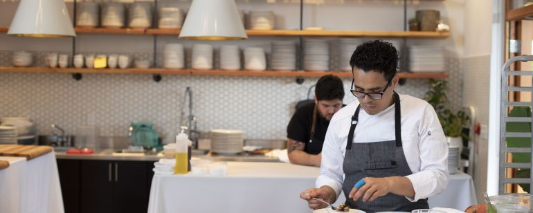 A chef plates some food in a kitchen