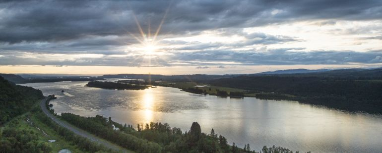 The sun breaks through clouds above a wide river
