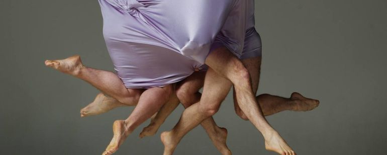 people covered in fabric with only legs showing in an artistic dance performance