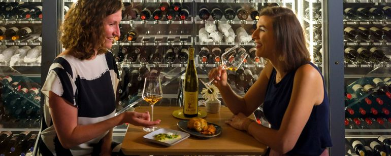two people eater food in front of a wine cellar