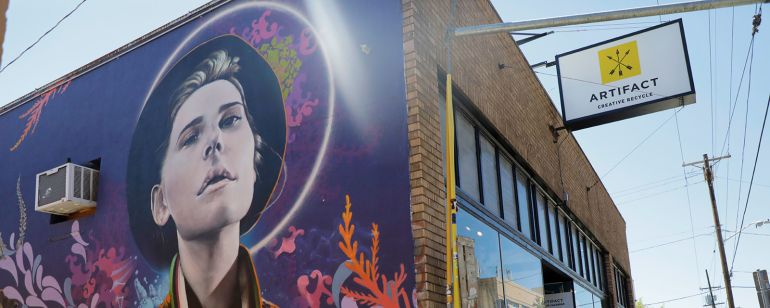 a multicolored mural depicting a person in a hat is painted on the side of a brick building