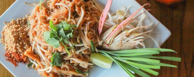 a closeup of a plate of thai food and thai iced tea