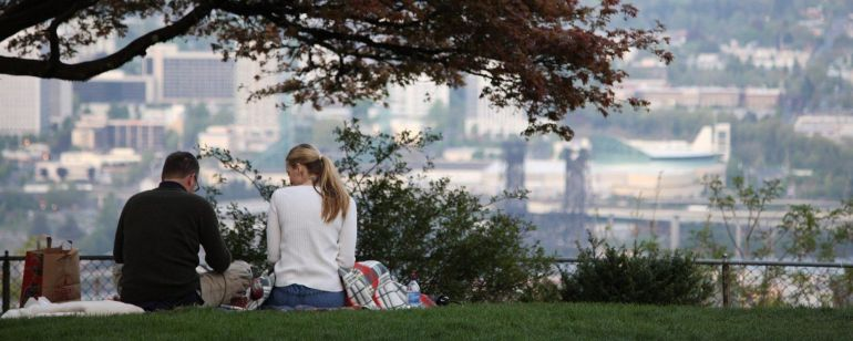 two people enjoy a picnic with a scenic city view