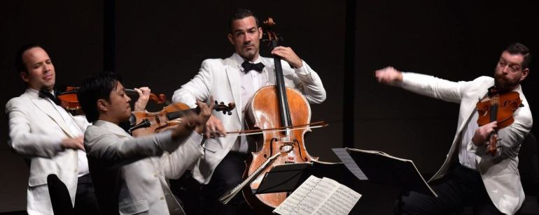 a quartet of string musicians wearing white tuxedos