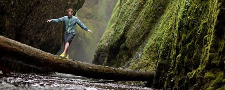 a person crossing a log in the Columbia Gorge