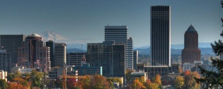 A view of downtown with its trees a fiery autumn orange with a snow capped Mt. Hood in the background.