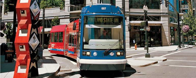 """A streetcar passes by a large, red sculpture in front of a building with a neon sign reading, \""""Go By Streetcar\"""""""