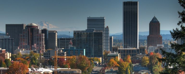 A view of city skyline with its trees a fiery autumn orange with a snow-capped mountain in the background.