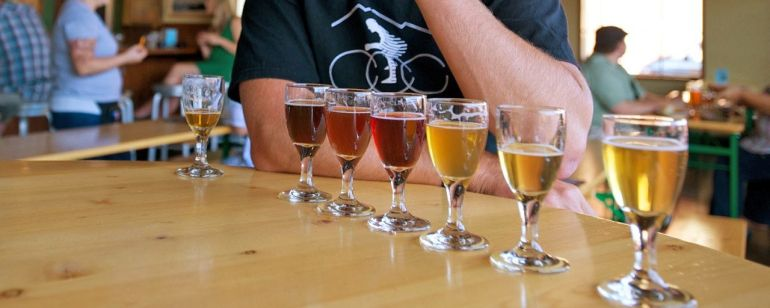 a person trying a tasting flight of beer at a bar