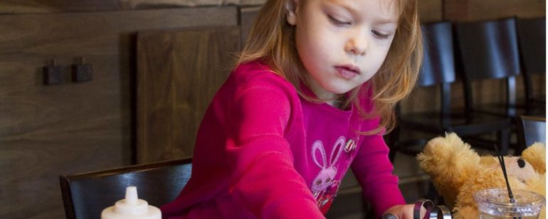 A young girl adds chocolate chips and blueberries to a pancake.