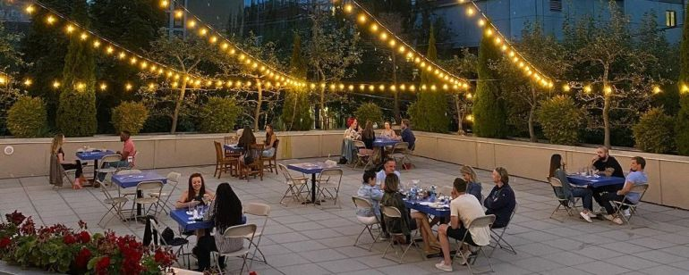 Roof top patio with socially distances tables and strung lights.