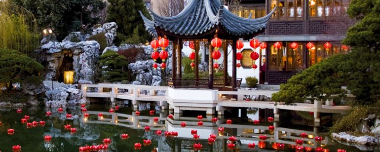 red lanterns float in water in front of a Chinese-style building