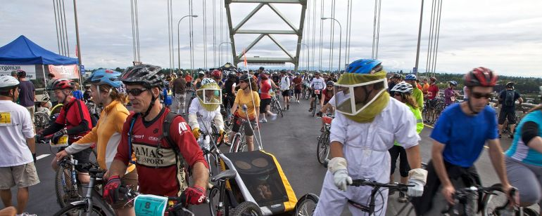 a crowd of bikers riding across a bridge during Bridge Pedal