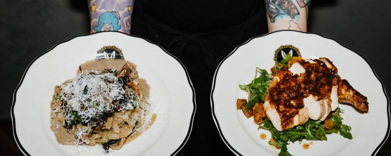 a person with tattooed forearms holds two plates of food