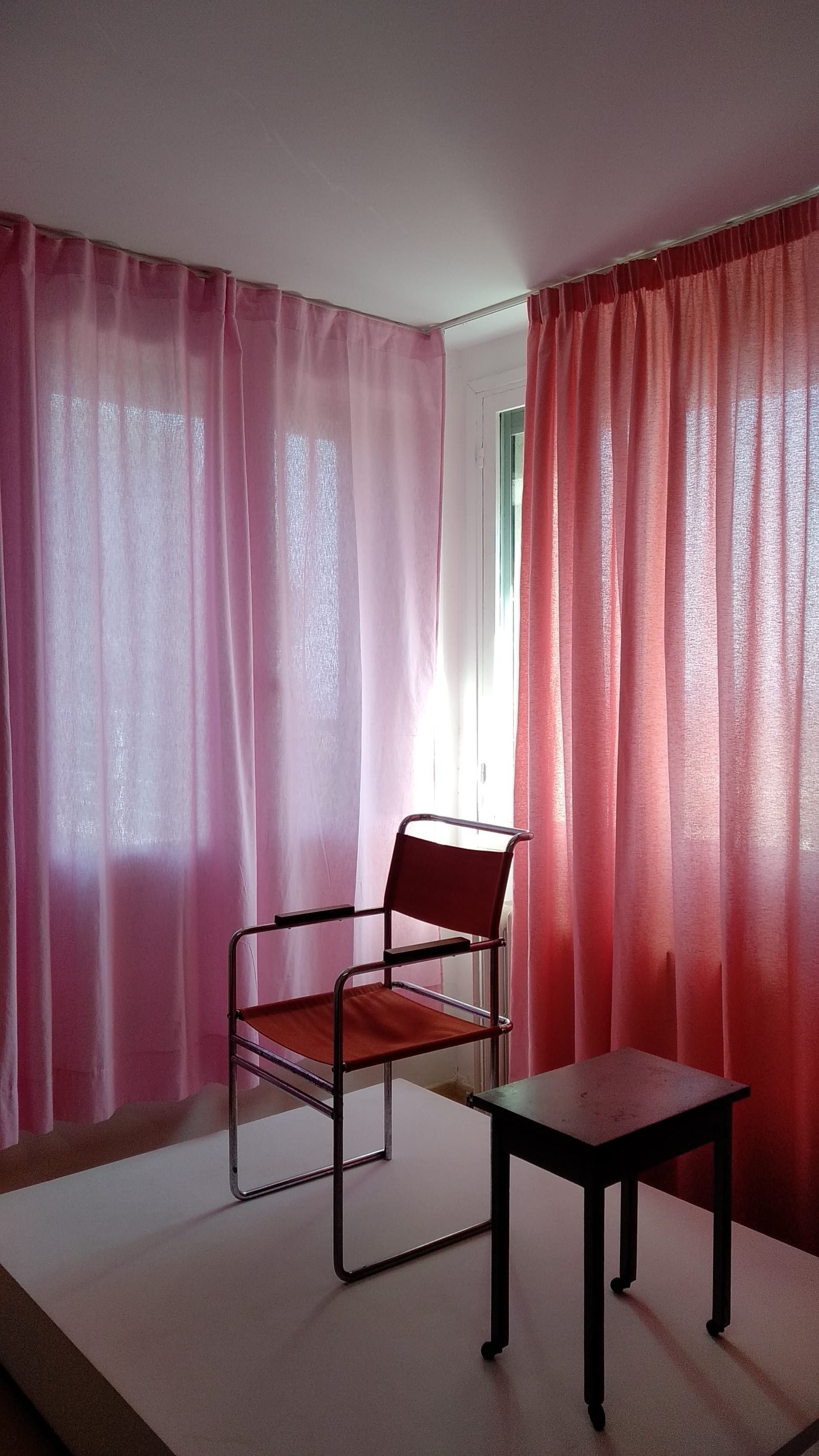 uncertain - In Villa Noailles, a red chair and a brown table are displayed in front of a pink curtain and a coral curtain - chair, table, curtains - paul lahana