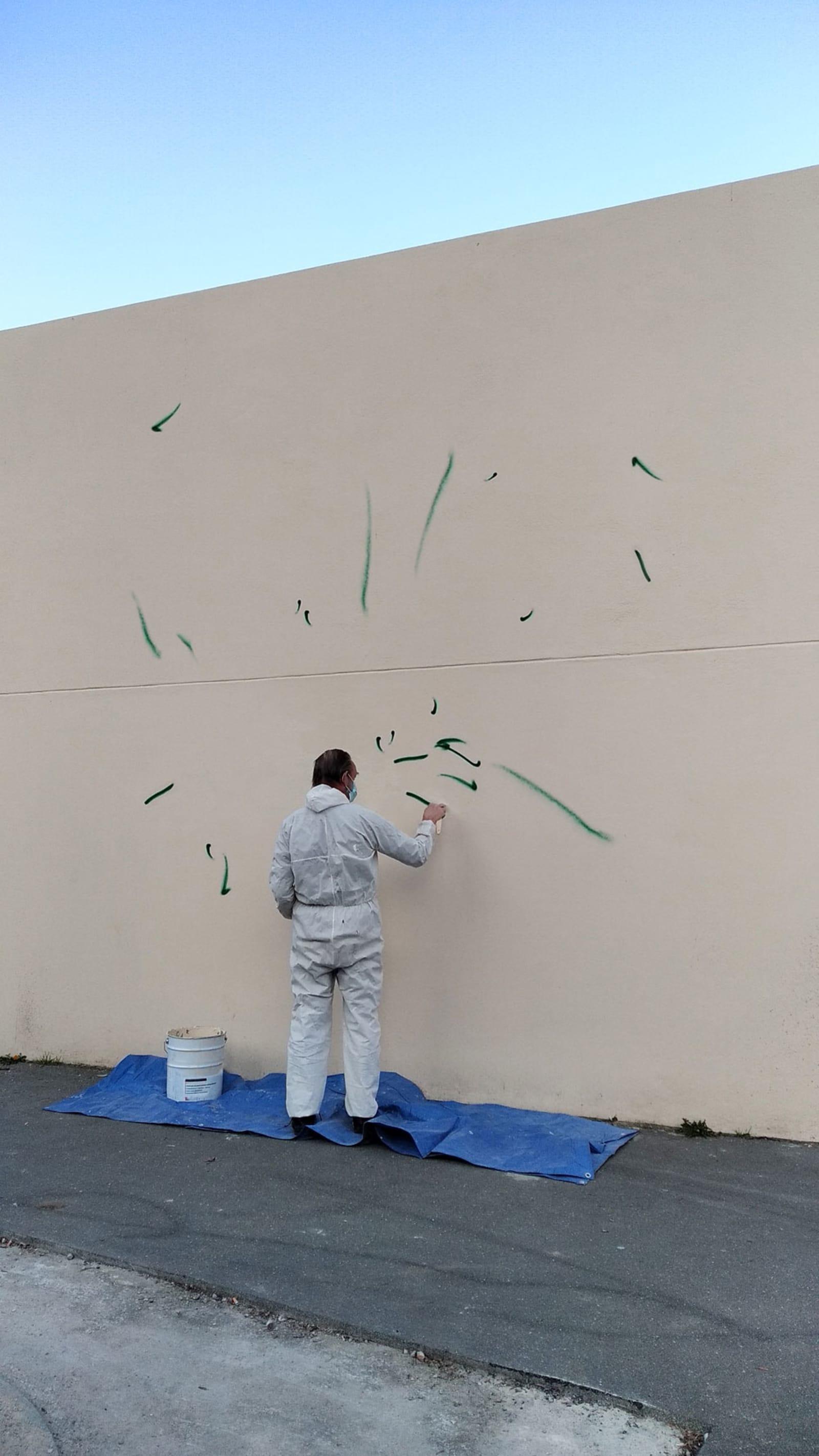 l'homme peint - a man is painting a wall with tiny graffiti - homme, peinture, mur, graffiti - paul lahana