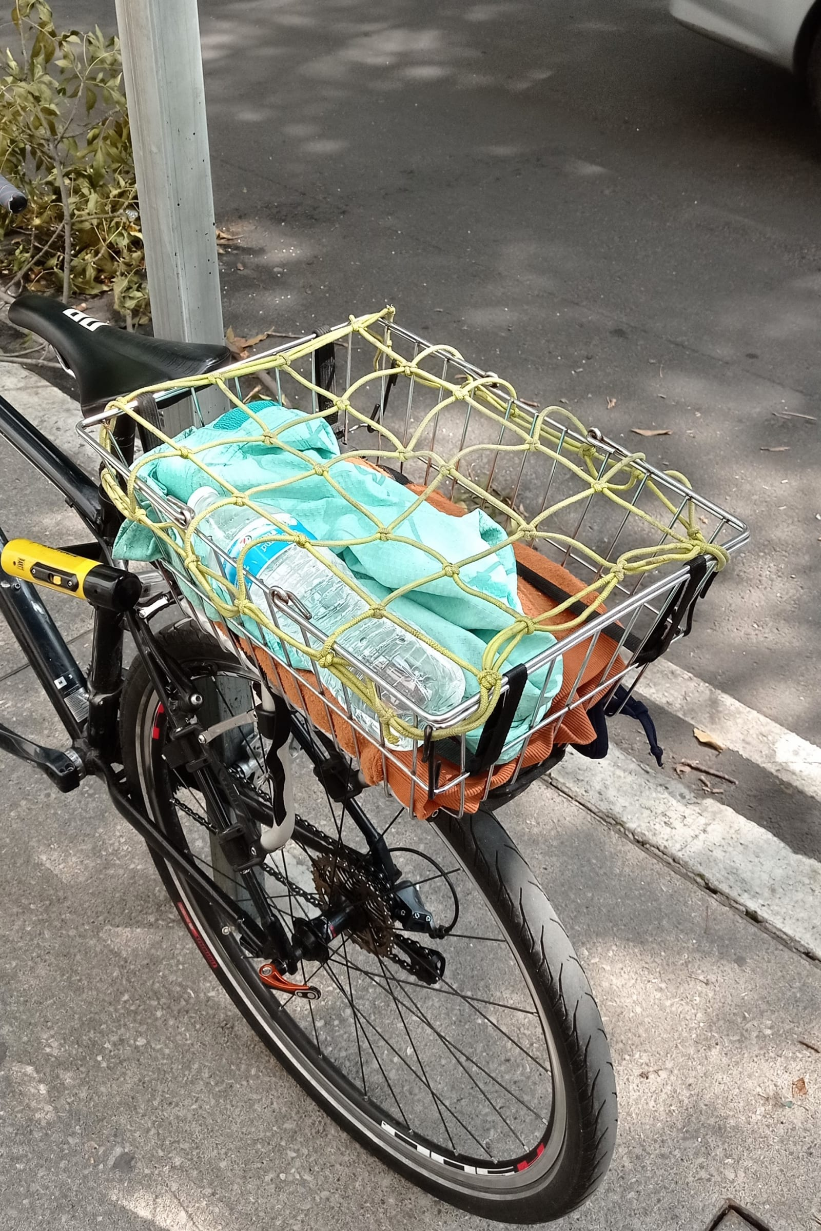 safe ride - a yellow net is offering protection to a green bag and an orange fabric - yellow net, green bag, orange fabric - paul lahana