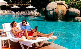 Couple Sitting beside Swimming Pool