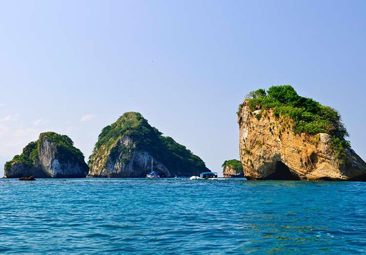 Boat out to these rocky islands, a protected natural area teeming with penguins, parrots, and sea turtles. Snorkel, dive, or hit the beach.