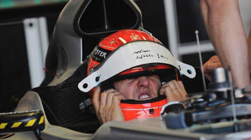 Michael Schumacher of Mercedes is fiited out in his car for the first practice session.
